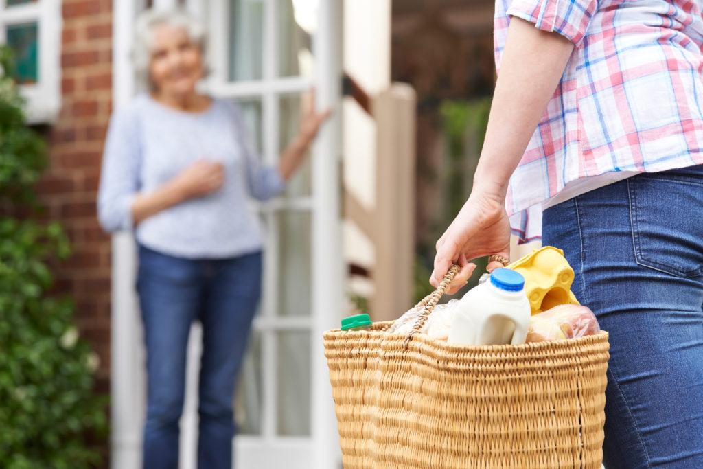 woman holding basket of groceries foreground going to senior in a home