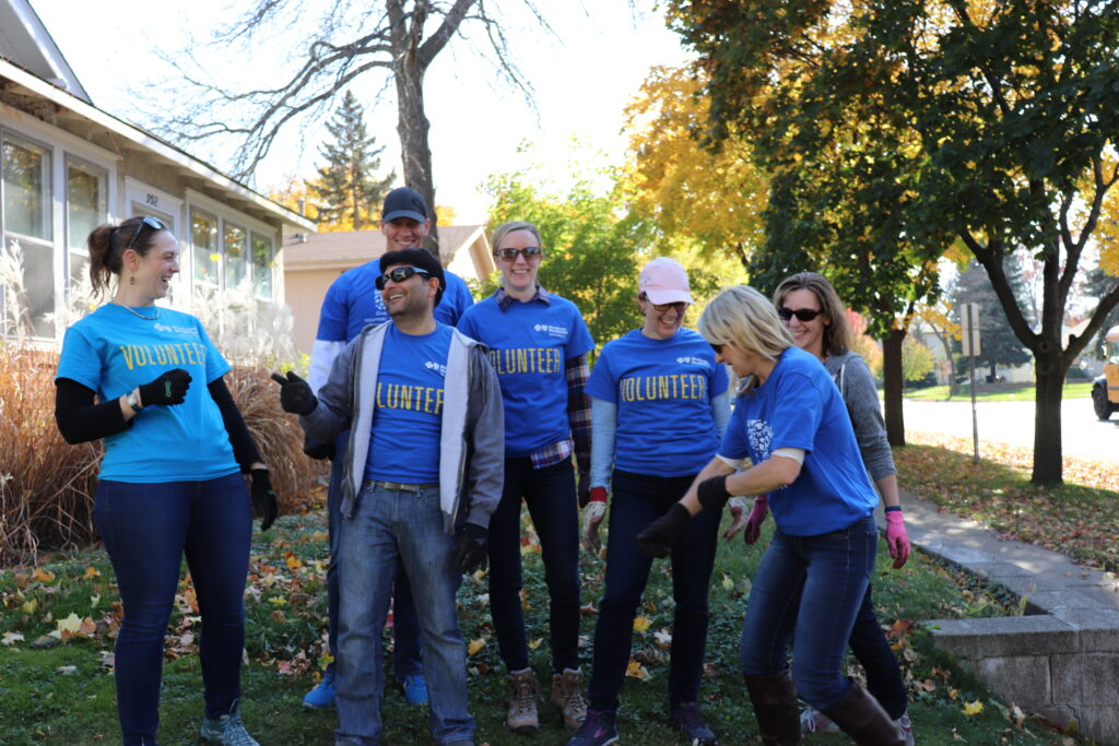blue cross volunteer fall cleanup crew posing for picture darts